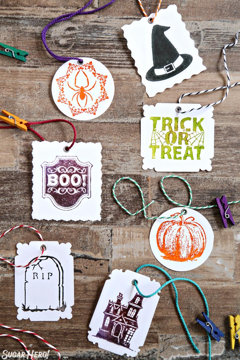 Stamped Halloween Cupcakes - assortment of stamped Halloween gift tags with colorful string | From SugarHero.com