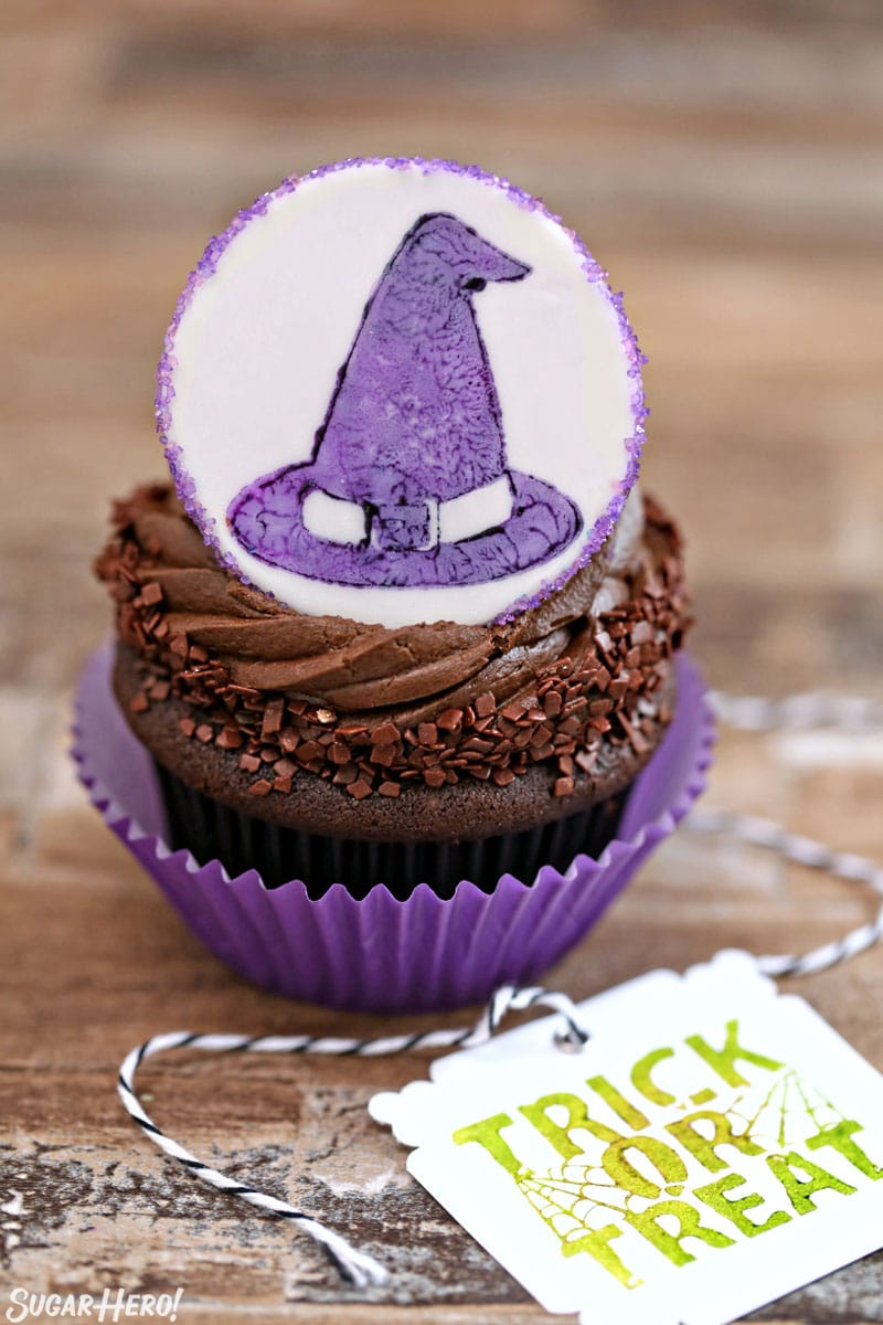 Stamped Halloween Cupcakes - close-up of chocolate cupcake with fondant circle on top with witch hat design | From SugarHero.com