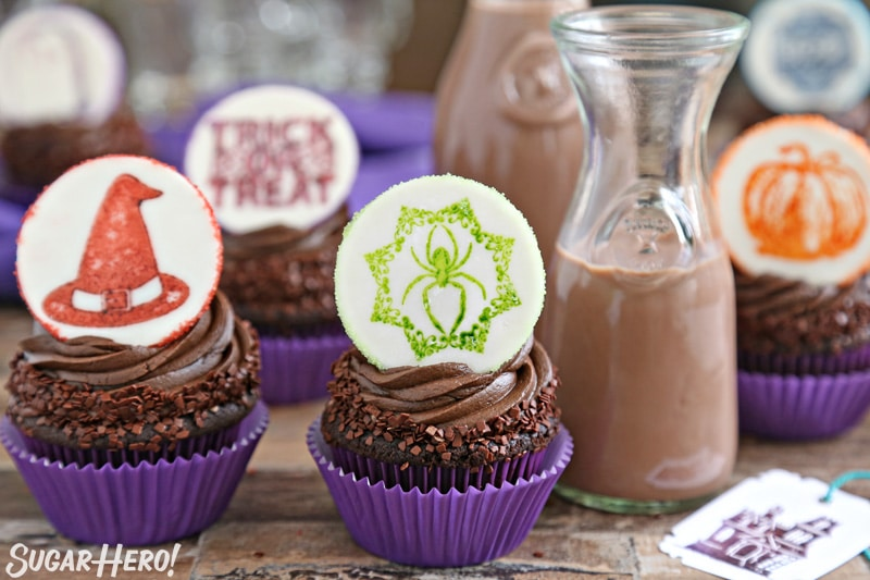 Stamped Halloween Cupcakes - group of double chocolate cupcakes topped with a Halloween fondant plaque, with chocolate milk | From SugarHero.com