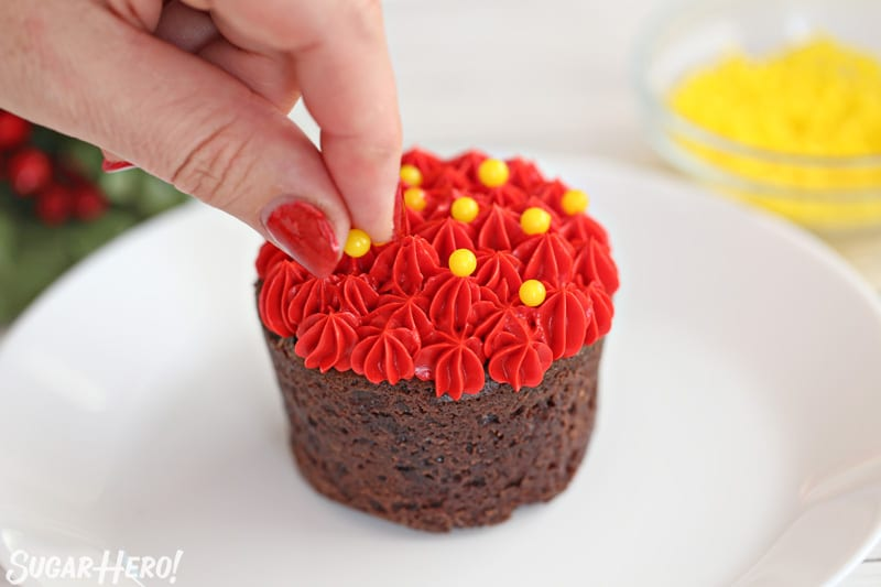 Blooming Chocolate Flowers - decorating the tops of peppermint mocha brownie cups with red frosting stars and yellow sugar pearls | From SugarHero.com
