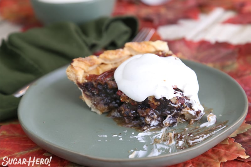 Deep Dish Pecan Pie - half-eaten piece of pie with whipped cream on top | From SugarHero.com