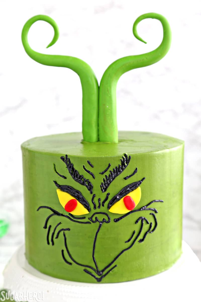 Grinch Cake - closer shot of the Grinch face piped onto a green cake with fondant hair | From SugarHero.com