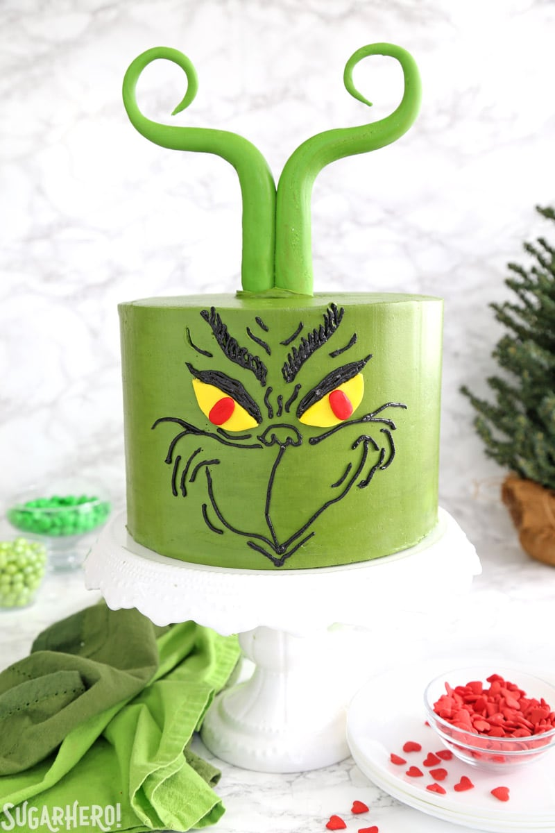 Grinch Cake - green cake decorated with a Grinch's face and fondant Grinch-like hair | From SugarHero.com