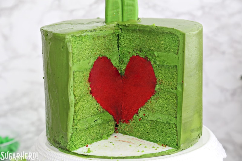 Grinch Cake - close-up of the inside of the green Grinch cake, containing a bright red cake heart | From SugarHero.com