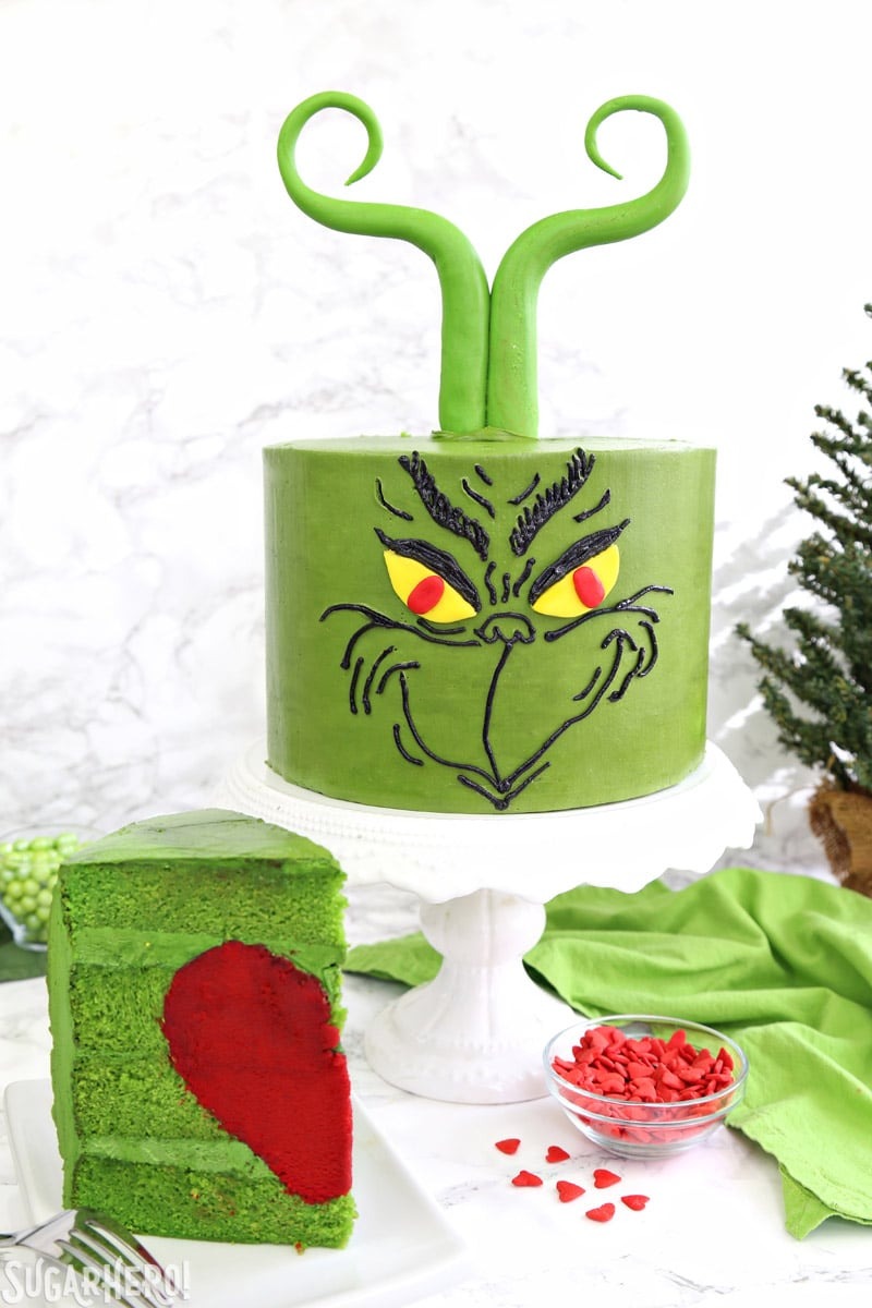 Grinch Cake - front of Grinch cake on a cake stand, with a slice of cake showing the red heart inside | From SugarHero.com