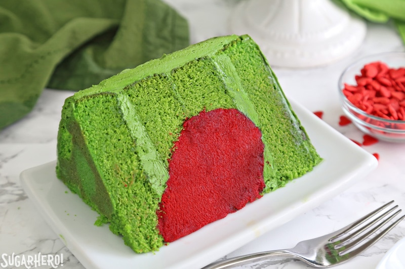Grinch Cake - close-up of one slice of Grinch cake, made from green cake layers and a bright red heart inside | From SugarHero.com