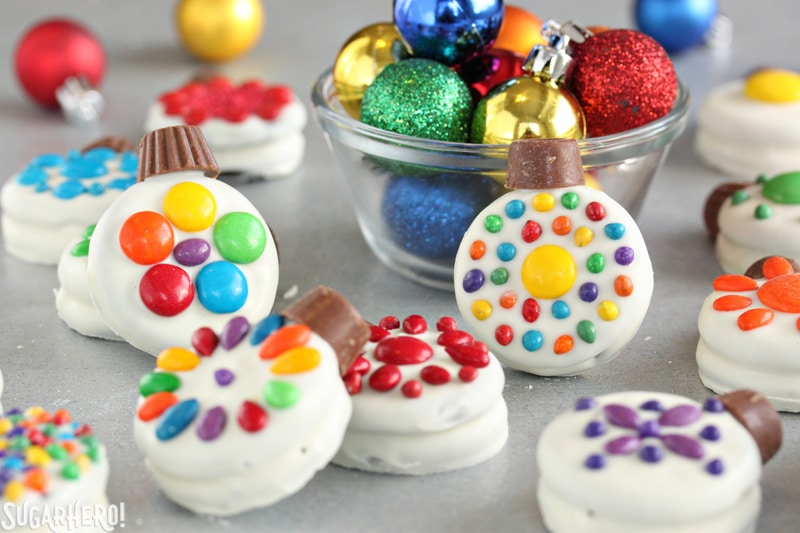 Oreo Cookie Christmas Ornaments - Oreo cookies decorated like Christmas ornaments, with real ornaments in a nearby bowl | From SugarHero.com