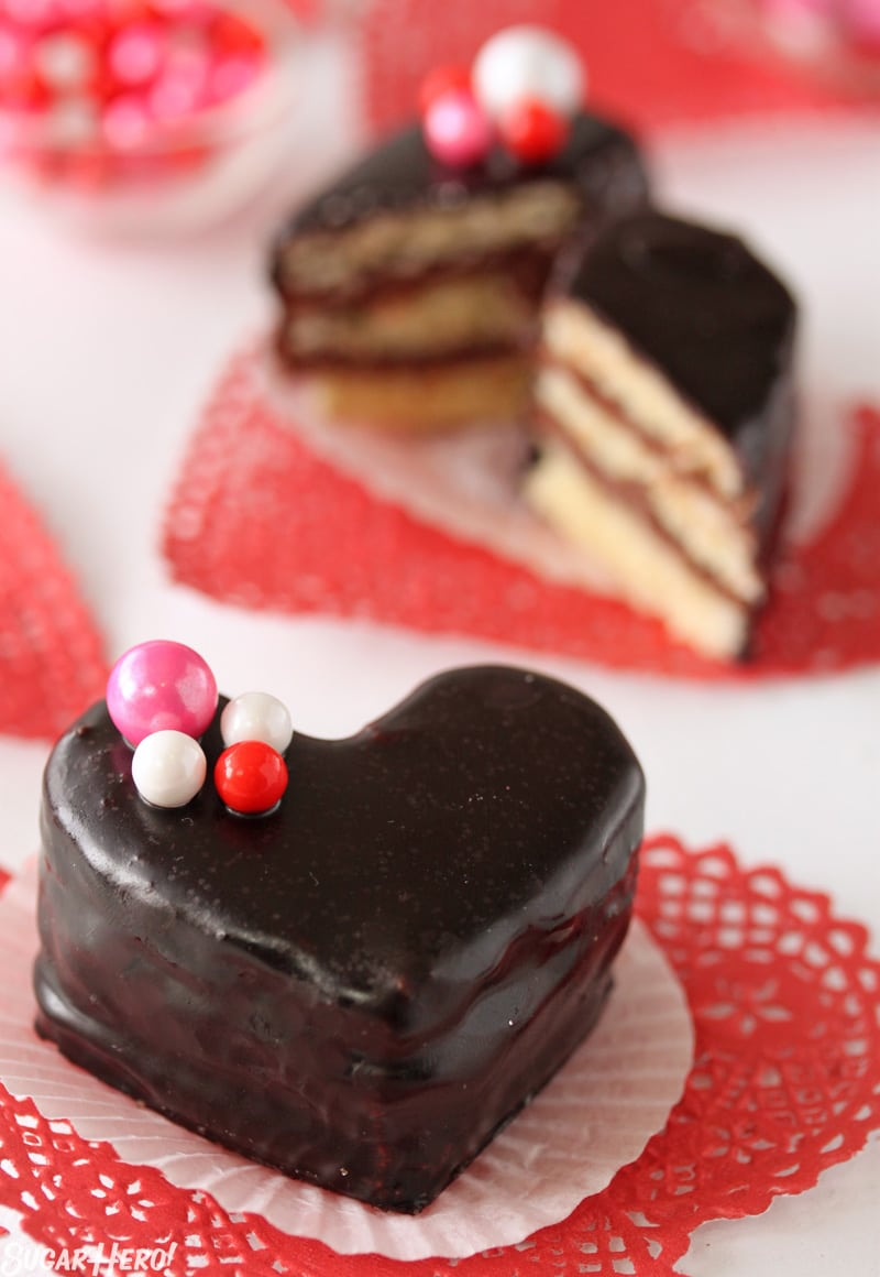 Nutella Pound Cake Petit Fours - A petit four covered in a chocolate glaze with pink and red candy on top. | From SugarHero.com
