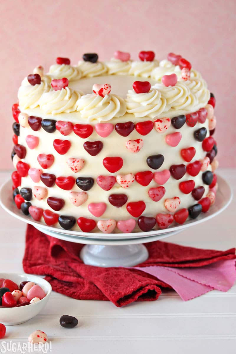 Sky-High Pink and Red Velvet Cake - Pink and Red Velvet Cake covered in frosting and topped with heart shaped candies. | From  SugarHero.com