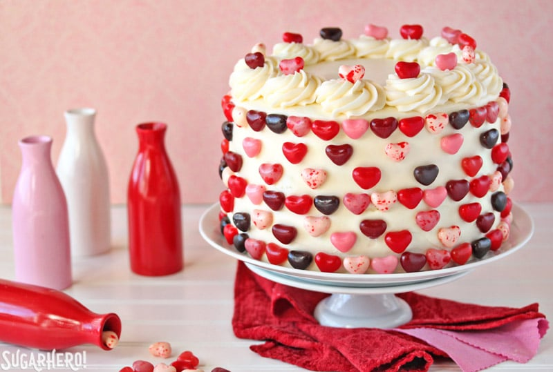 Sky-High Pink and Red Velvet Cake - cake displayed on a plate with heart shape candies around and on the cake. | From SugarHero.com