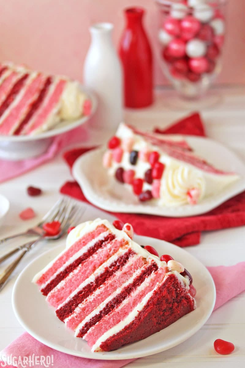 Sky-High Pink and Red Velvet Cake - Pieces of cake displayed on plates showing the red and pink striped layers throughout the cake. | From SugarHero.com