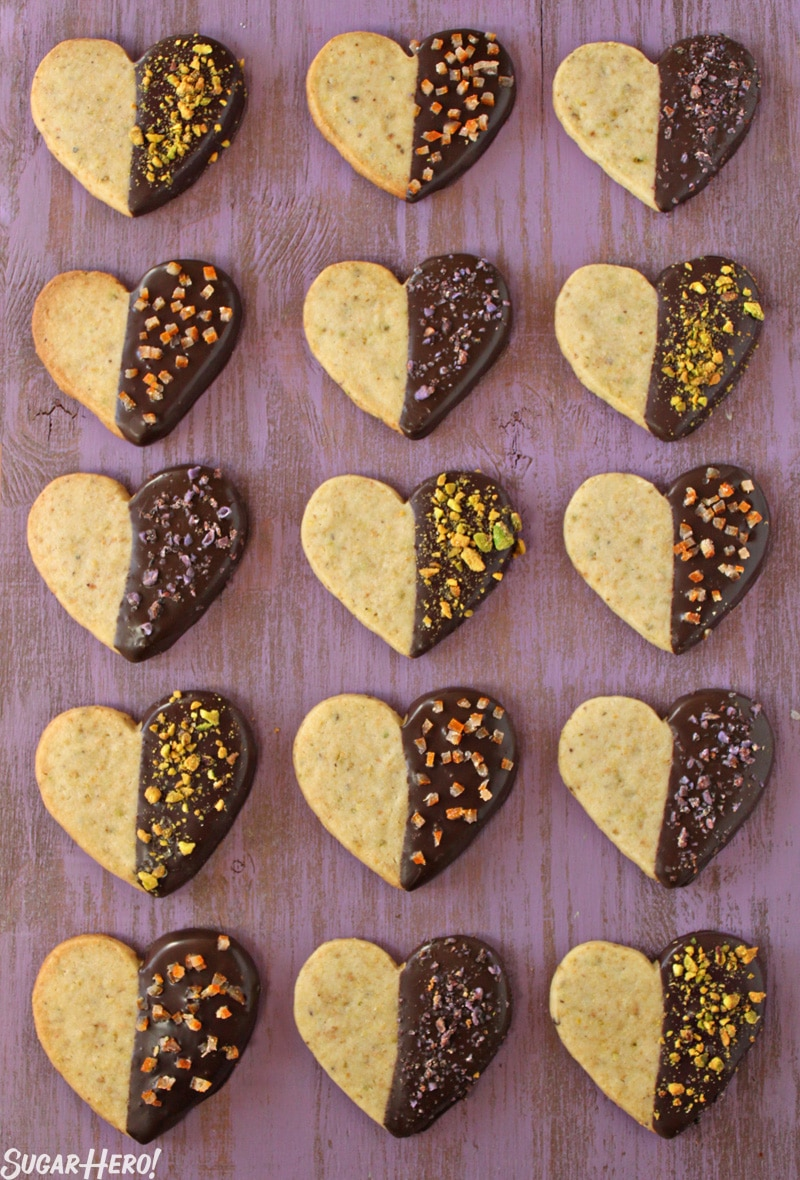 Pistachio Shortbread Cookies - 15 cookies displayed in rows. The cookies are half covered in chocolate and topped with pistachios. | From SugarHero.com