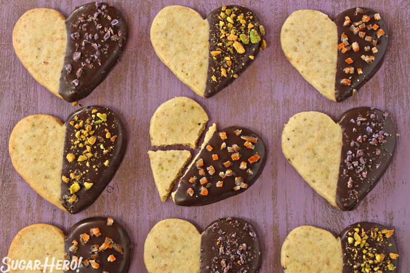 Pistachio Shortbread Cookies - 9 shortbread cookies displayed in rows of three. One of the cookies is broke into three pieces. | From Sugarhero.com