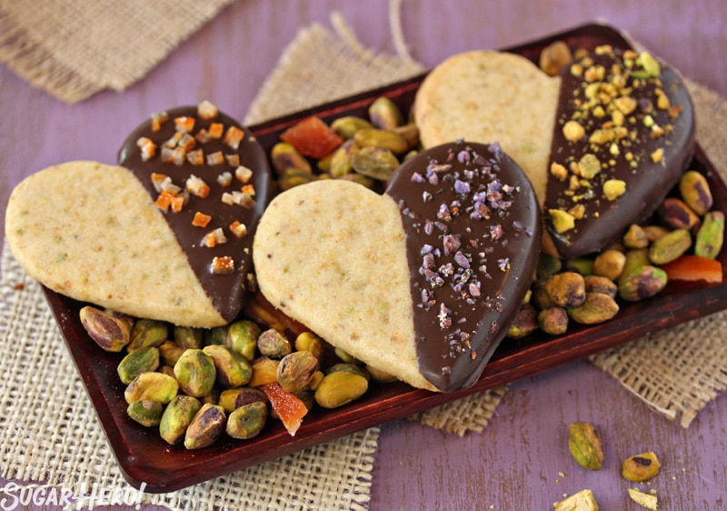 Pistachio Shortbread Cookies - Three shortbread cookies displayed on a tray with pistachios. | From SugarHero.com
