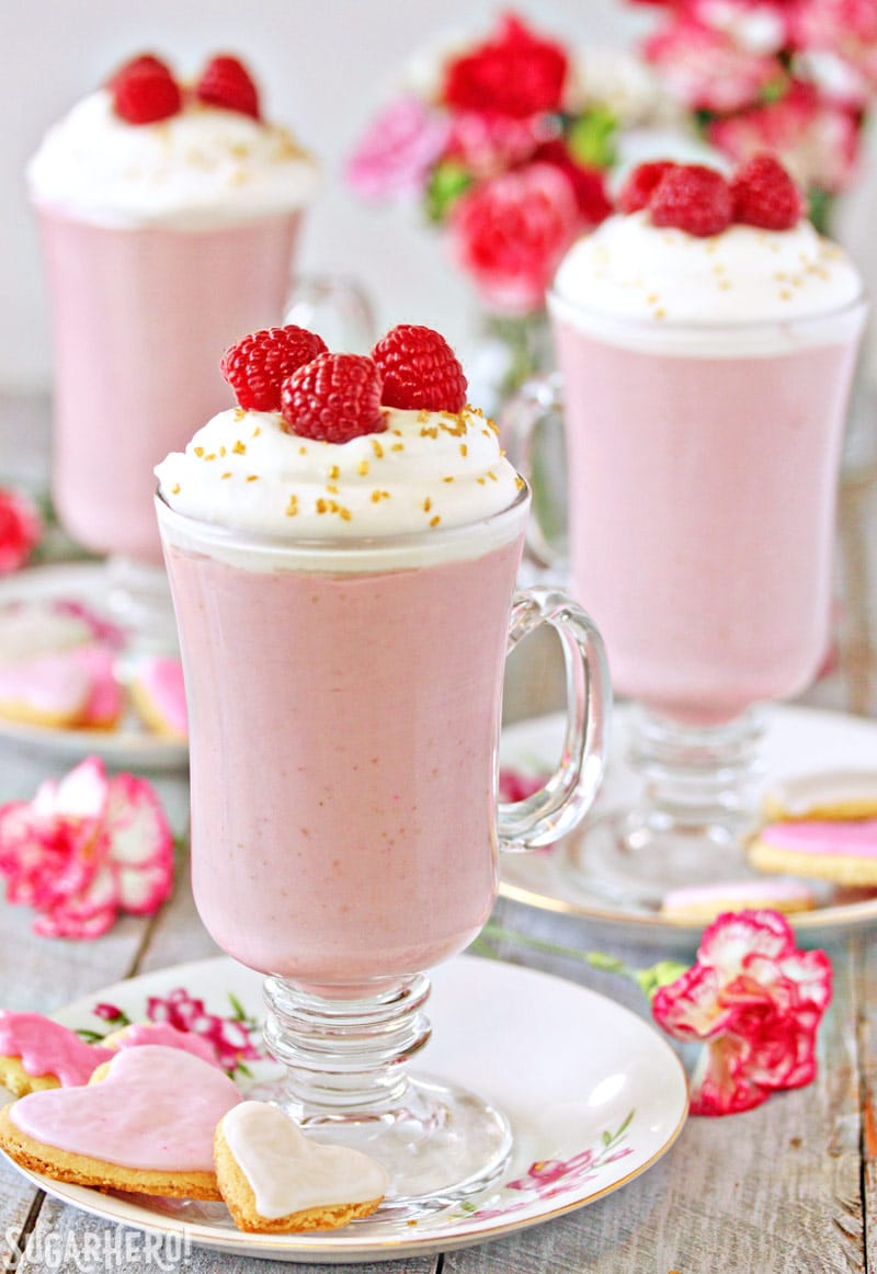 Raspberry White Hot Chocolate - Three separate glasses with hot chocolate and raspberries on top | From SugarHero.com
