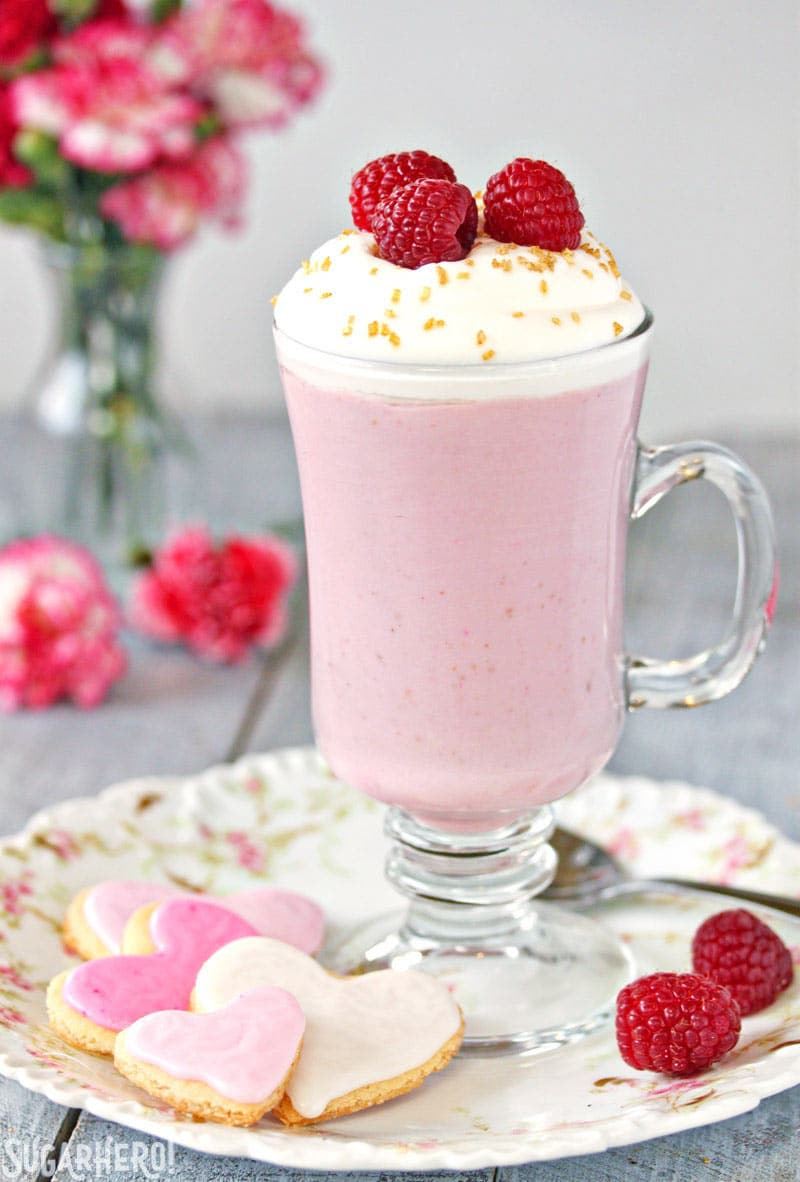 Raspberry White Hot Chocolate - A single cup of hot chocolate with raspberries on top and heart shaped cookies to the side   From SugarHero.com