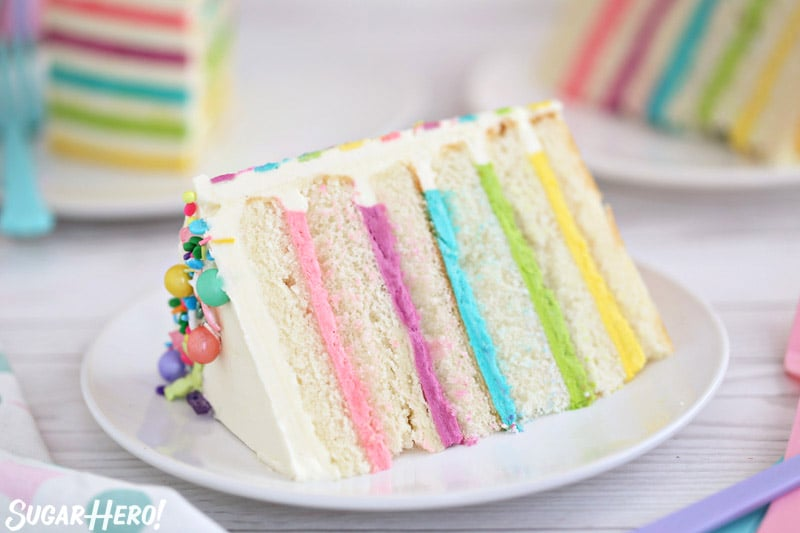 Striped Buttercream Balloon Cake - close-up picture of a single slice of cake, with several slices in the background | From SugarHero.com