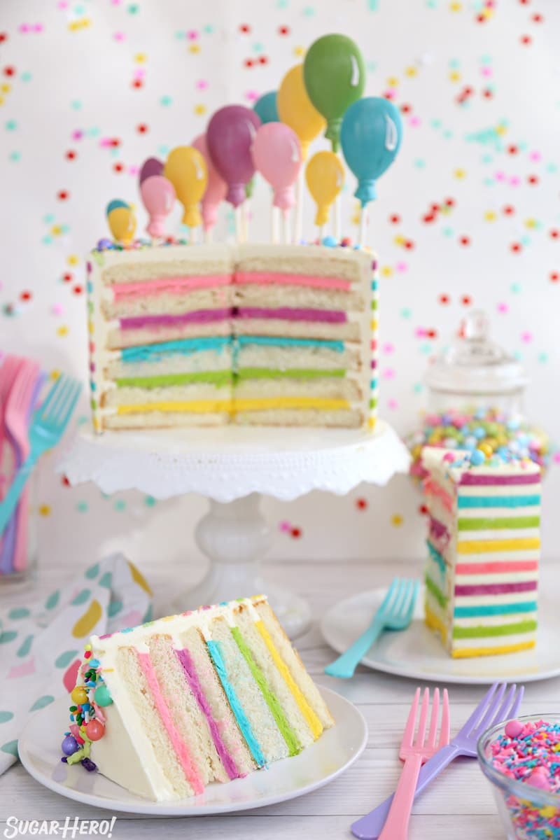 Striped Buttercream Balloon Cake - cut cake with several slices arranged in front of it | From SugarHero.com