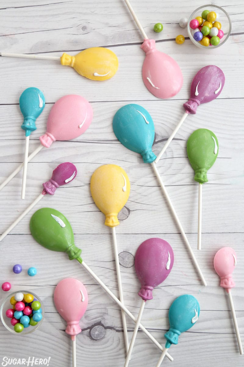 Striped Buttercream Balloon Cake - candy balloon lollipops arranged on a white wooden background | From SugarHero.com