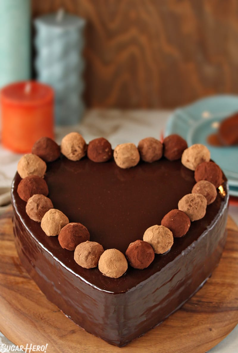 Truffle-Topped Heart Cake - A chocolate heart shaped cake with a glaze and homemade truffles lining the top. | From SugarHero.com
