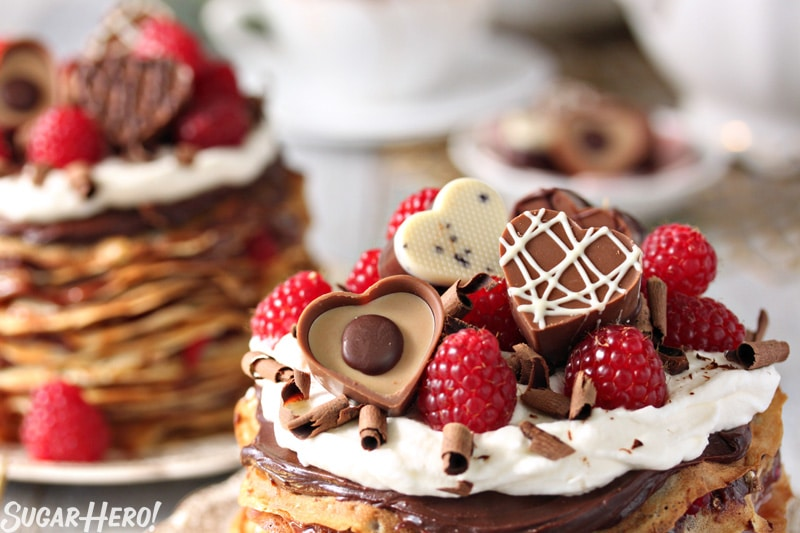 Chocolate Raspberry Mini Crepe Cakes - The top of a crepe cake showing the toppings. Heart shaped chocolates and raspberries. | From SugarHero.com