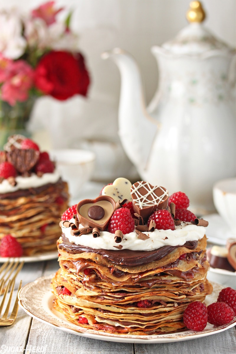 Chocolate Raspberry Mini Crepe Cakes - One crepe cake displayed with chocolates and raspberries on top showing the layers of crepes and filling. | From SugarHero.com