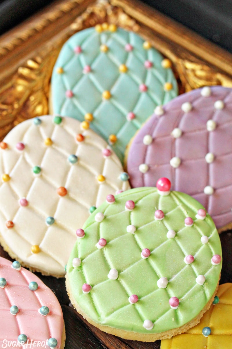 Easter Egg Sugar Cookies with colorful sugar pearl accents on a gold tray