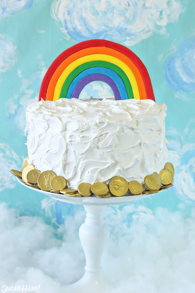 Rainbow cake on a white cake stand with chocolate gold coins around the base