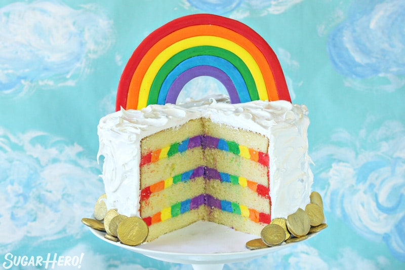 Rainbow cake with white frosting on the outside, rainbow buttercream on the inside, and a fondant rainbow cake topper