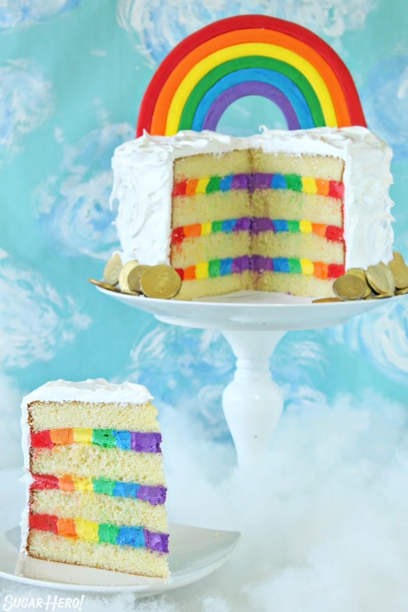 Rainbow cake on a white cake stand with a slice removed