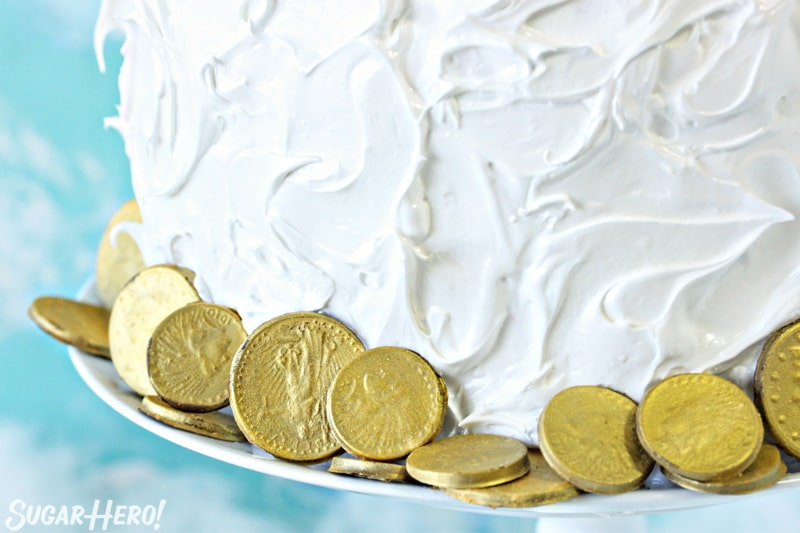 Close-up of edible chocolate gold coins around the base of the rainbow cake