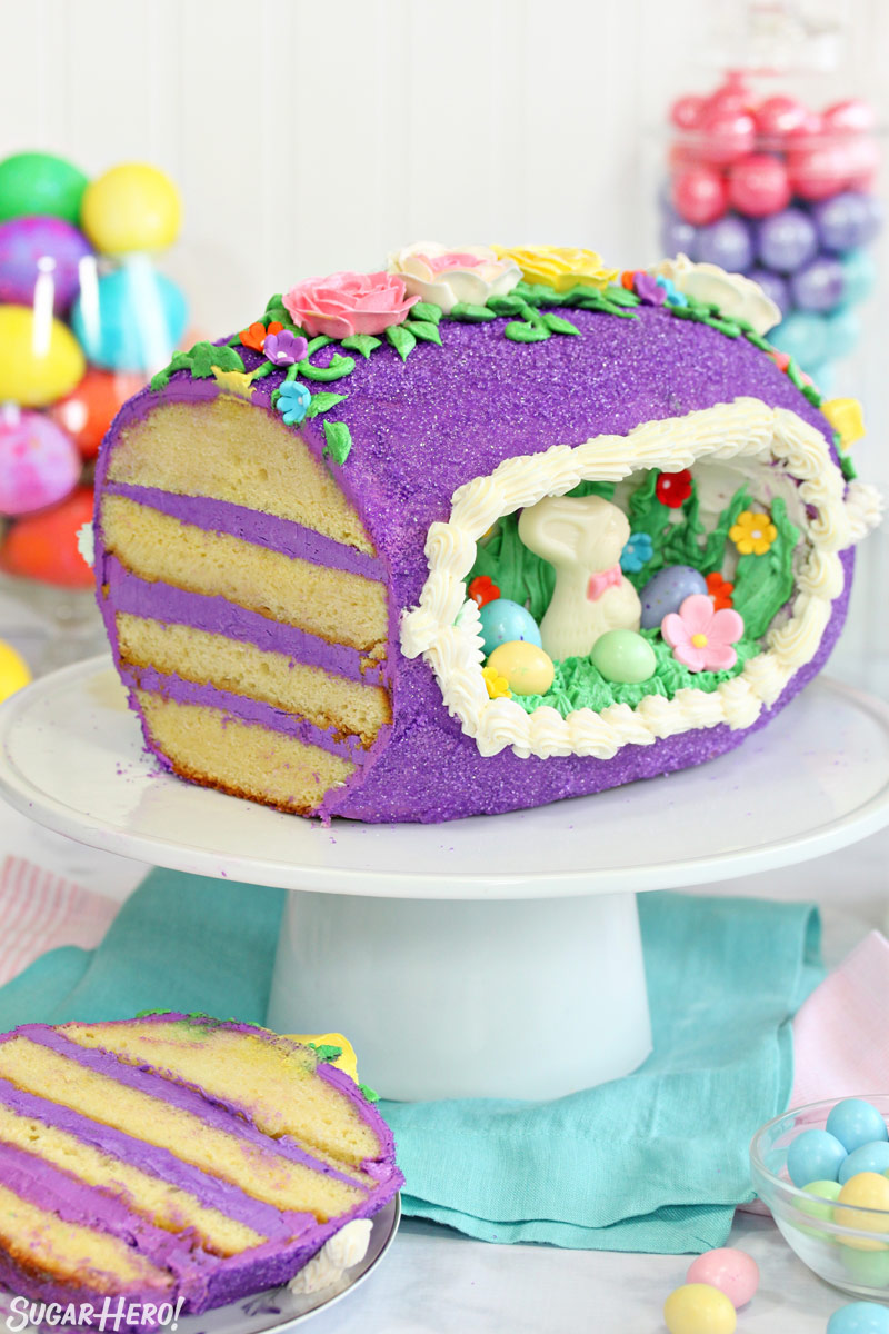 Sugar Easter egg cake, with a slice taken out of it and resting on a plate near the base of a cake stand