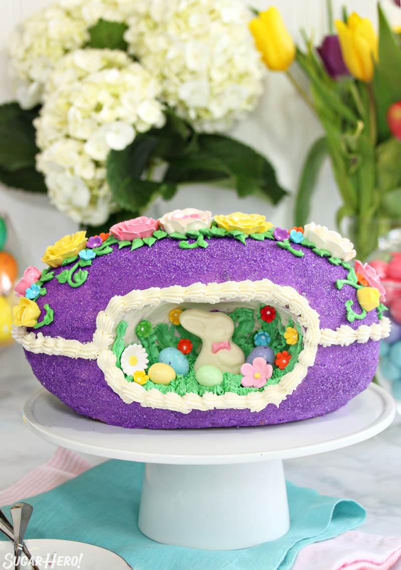 Sugar Easter Egg Cake on a white cake stand in front of hydrangeas and tulips