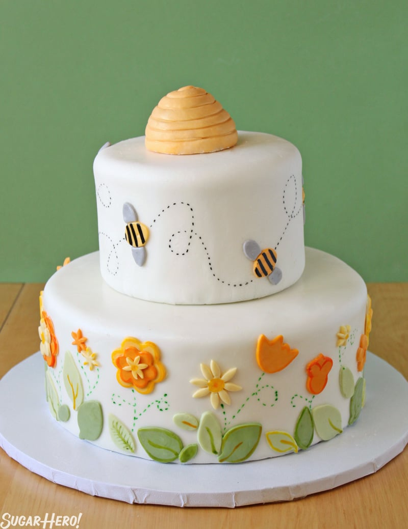 Bumblebee Cake - A shot of the full layer cake with a beehive on top made of fondant.  | From SugarHero.com