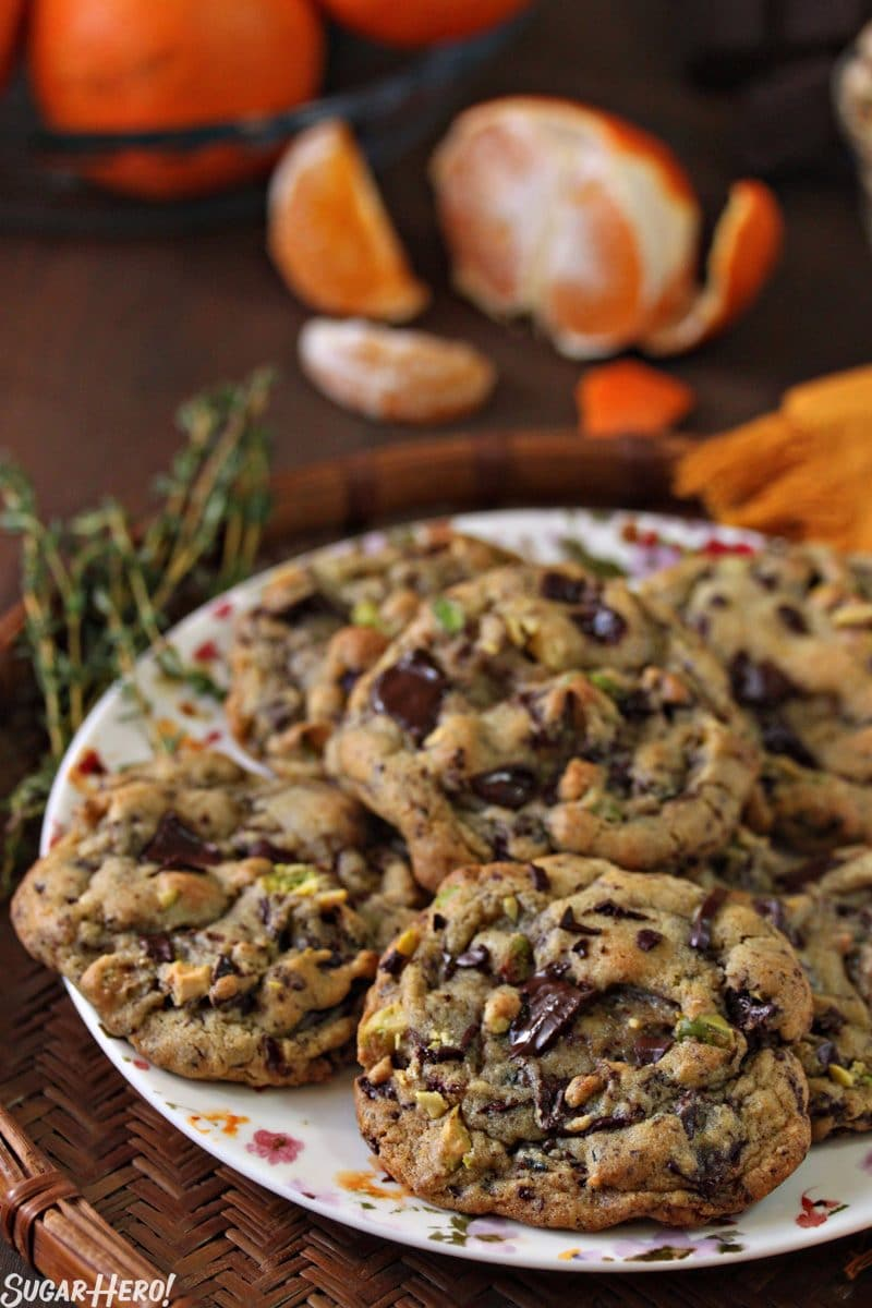Clemen-Thyme Chocolate Chunk Cookies - Straight shot of a plate full of cookies with thyme and a clementine displayed.   From SugarHero.com