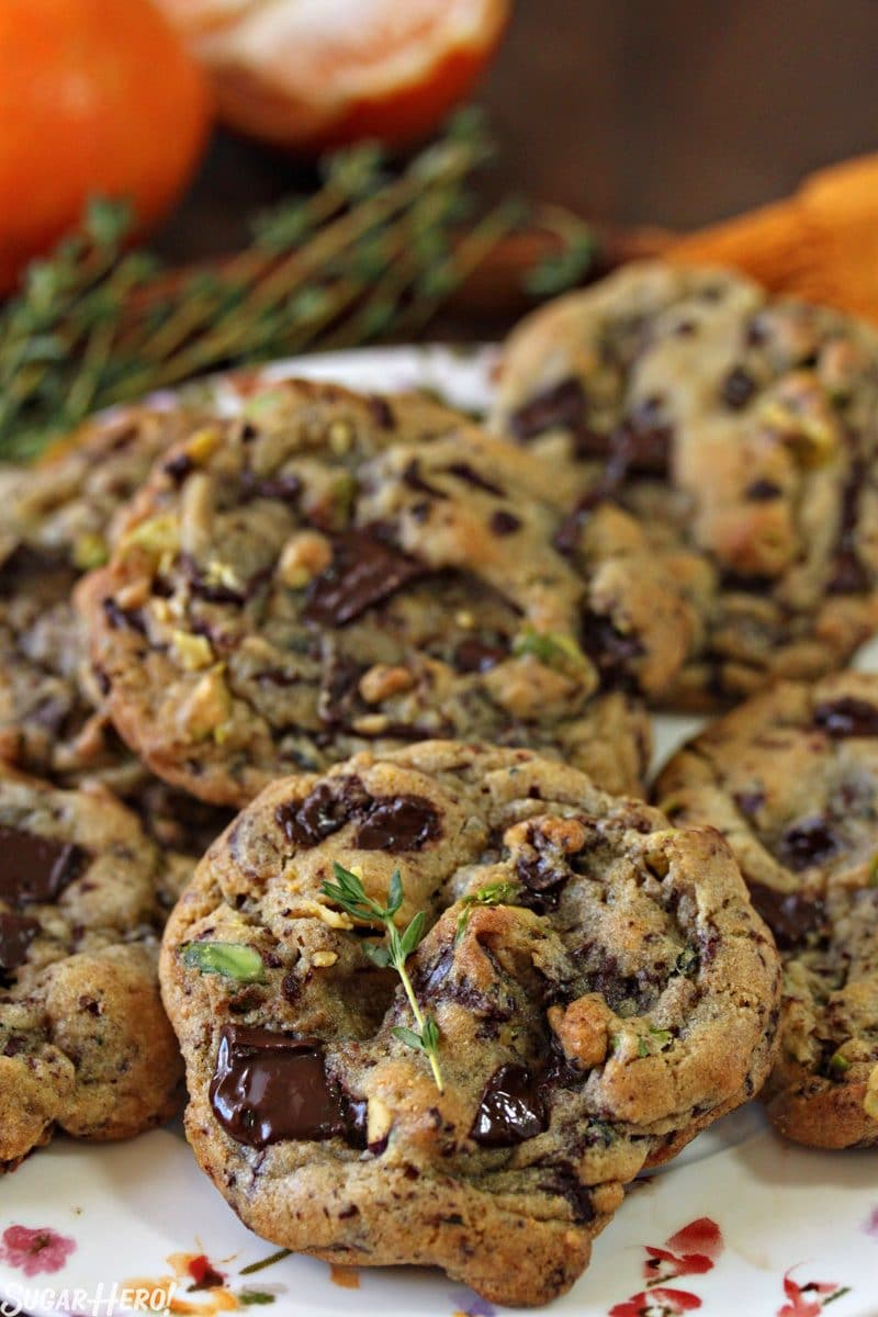 Clemen-Thyme Chocolate Chunk Cookies - A shot of a plate full of cookies with thyme displayed on top of a cookie.   From SugarHero.com