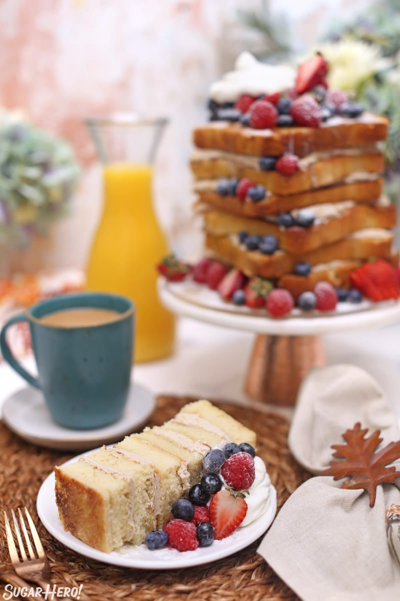 Slice of cake on white plate in front of cake on cake stand
