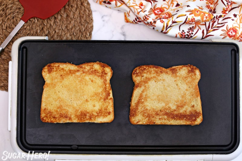Two large pieces of French toast cake being toasted on a nonstick skillet