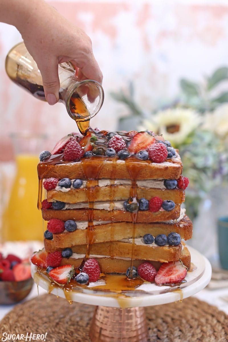 Syrup being poured from glass jar onto French toast layer cake
