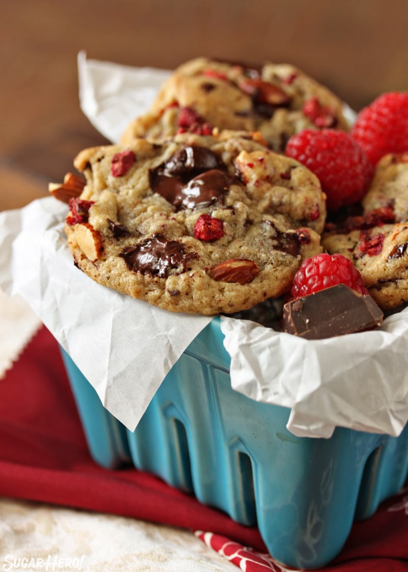 Raspberry Almond Chocolate Chunk Cookies - a straight shot of the cookies displayed in a blue basket. | From SugarHero.com