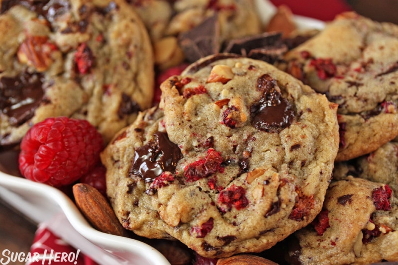 Raspberry Almond Chocolate Chunk Cookies - Straight shot of cookies displayed with almonds, and raspberries. | From SugarHero.com