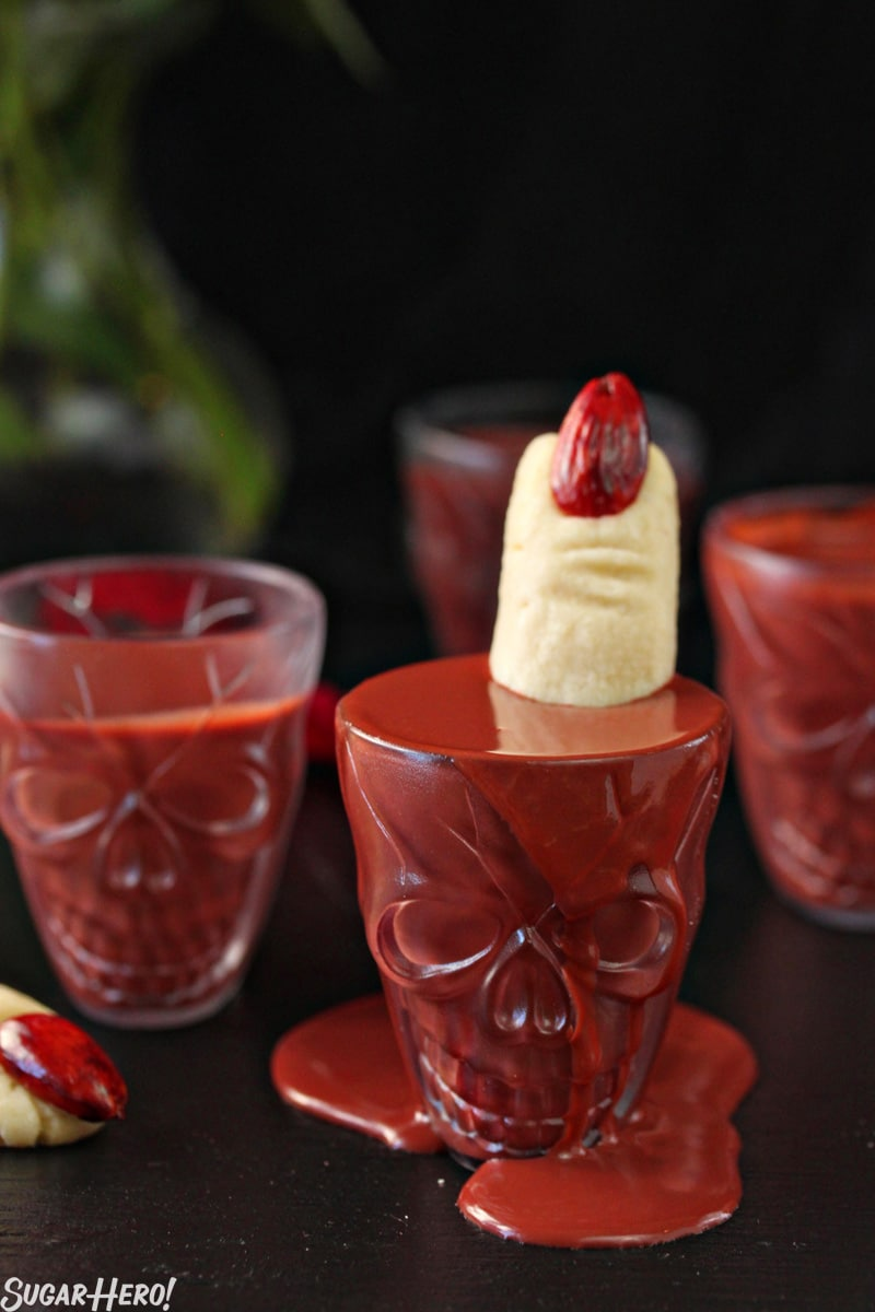 This Red Velvet Hot Chocolate - A shot of the hot chocolate over flowing with a witch finger cookie inside. | From SugarHero.com
