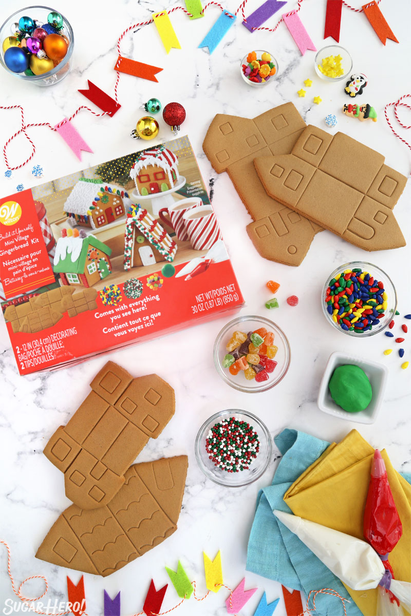 Overhead shot showing the ingredients for making gingerbread houses, including gingerbread, sprinkles, and royal icing