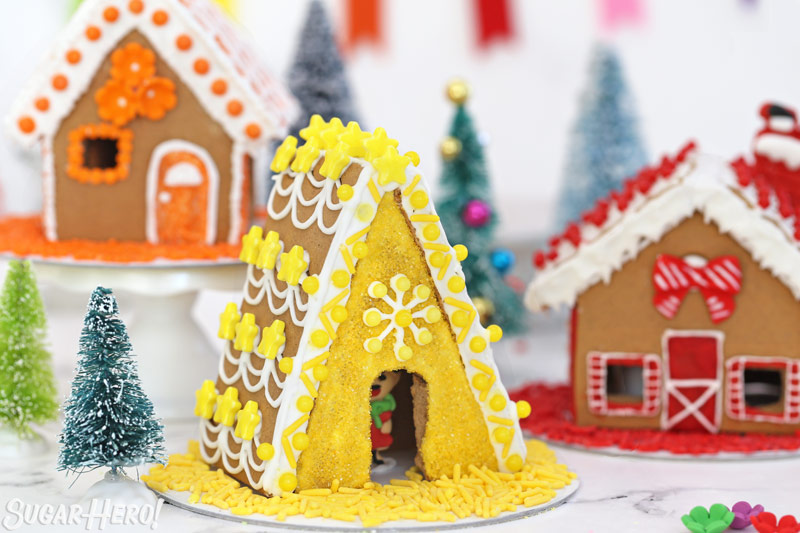 Yellow-themed gingerbread A- frame house, with a royal icing elf peeking out from inside