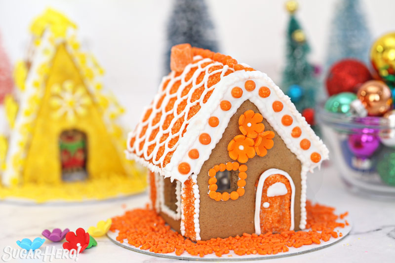 Orange-themed gingerbread house, with orange royal icing flowers on the front