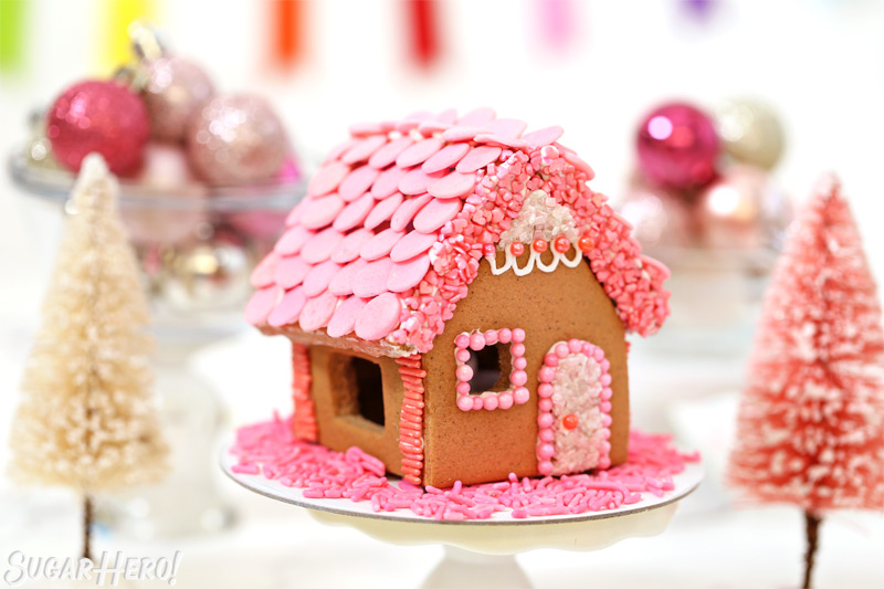 Pink-themed gingerbread house, with pink roof shingles and pink sprinkles