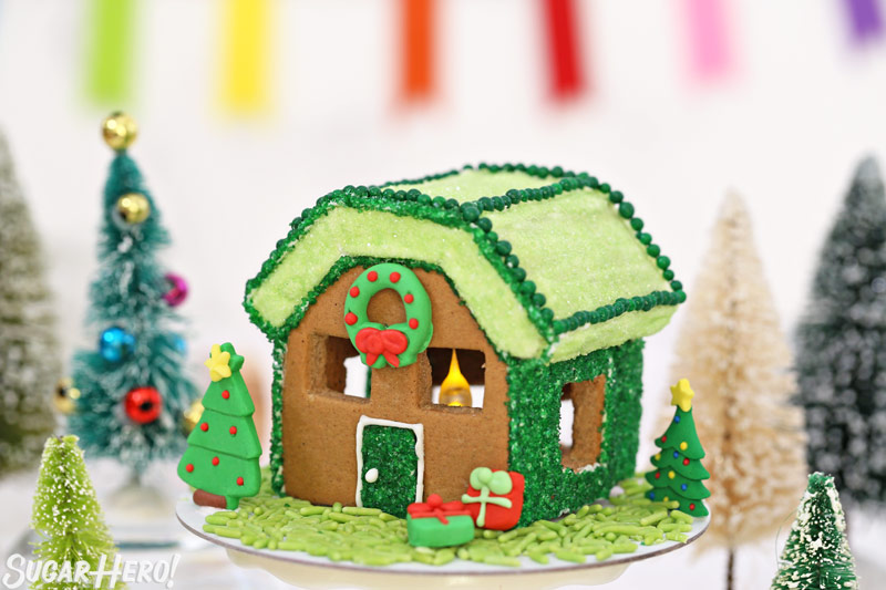 Close-up of green themed gingerbread house, with royal icing trees and wreath