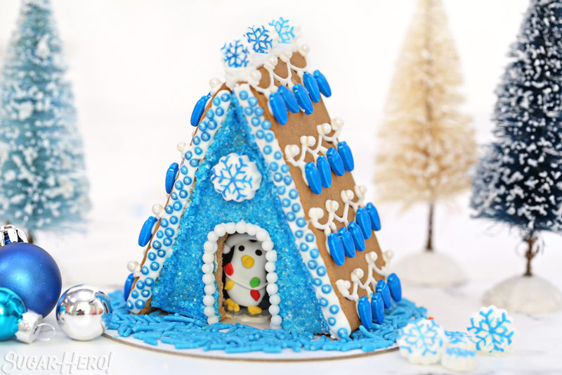 Blue-themed A-frame gingerbread house, with royal icing snowflakes and a royal icing penguin peeking out from inside