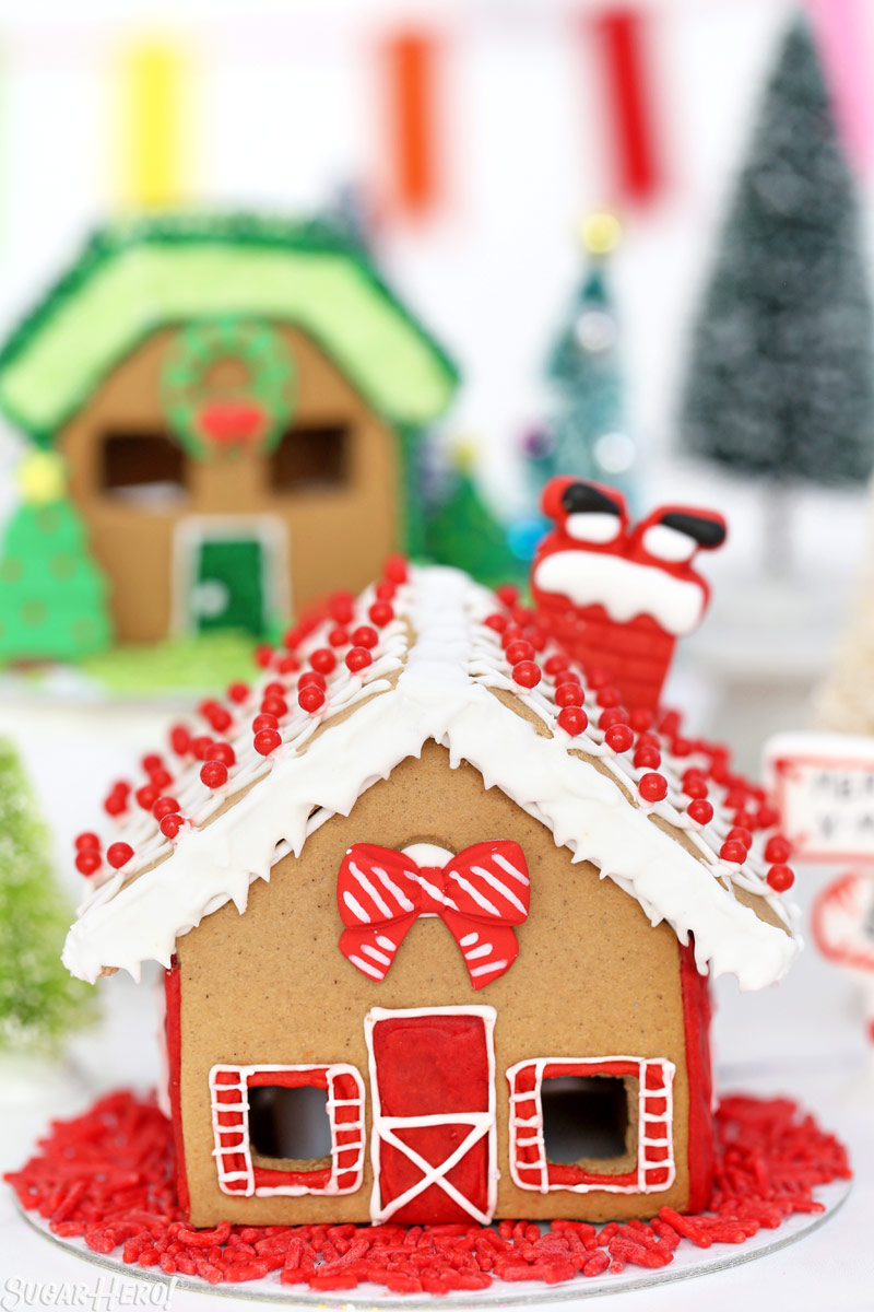 Red-themed gingerbread house, with a red royal icing bow and a royal icing Santa upside-down on the roof