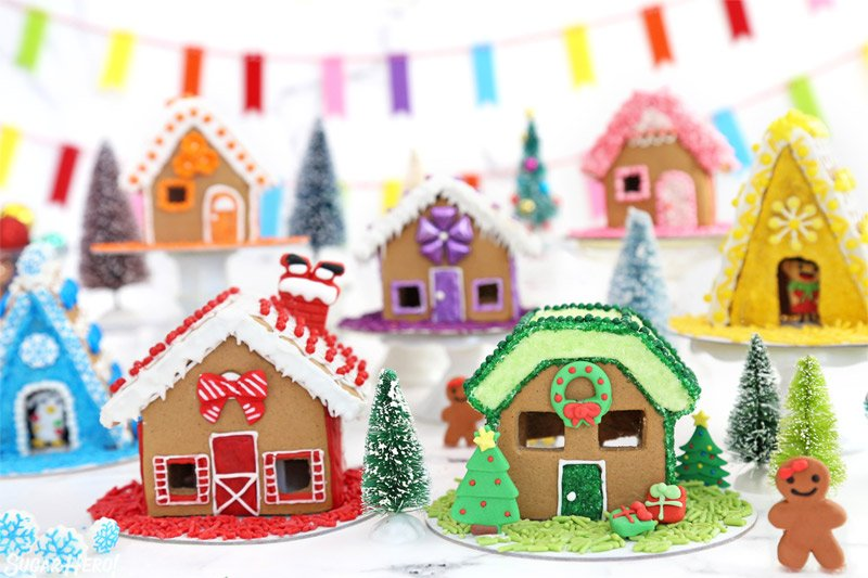 A group of mini gingerbread houses, decorated with a rainbow color scheme